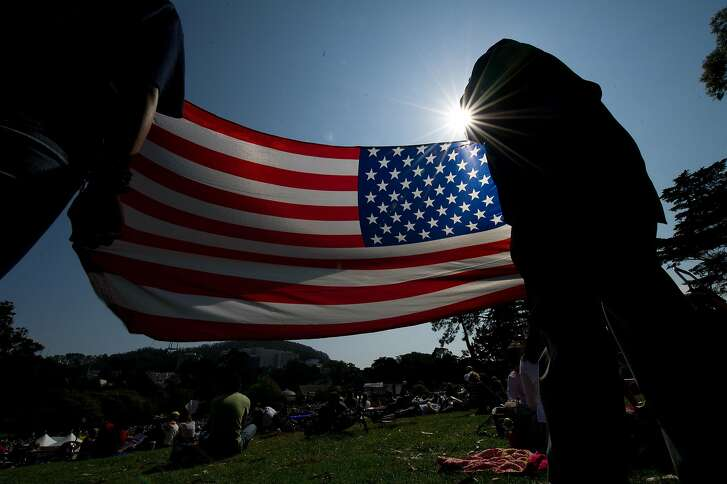 Jesse Massey a veteran of the United States Coast Guard and his daughter Anaya Cortez, 14 hold an American Flag as they watch the San Francisco Opera in the Park  performance in Golden Gate Park on September 11, 2011 in San Francisco, Calif.