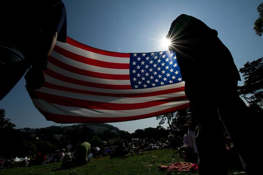 Jesse Massey a veteran of the United States Coast Guard, and his daughter Anaya Cortez hold an American flag as they watch the San Francisco Opera in the Park performance in Golden Gate Park on Sept. 11, 2011. Photo: David Paul Morris, Special To The Chronicle