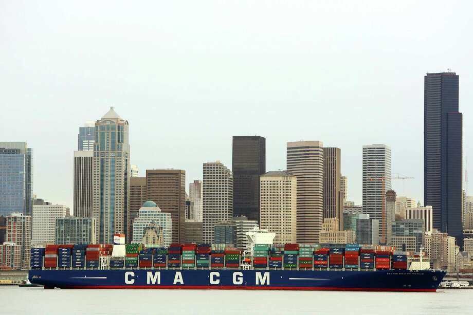 A cargo ship is towed to Seattle's Terminal 18. The U.S. trade deficit jumped in January to the highest level in nearly five years as a flood of mobile phones and other consumer products widened America's trade gap with China. Photo: Associated Press /File Photo / seattlepi.com