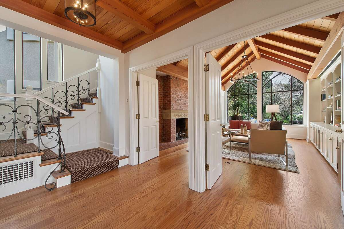Hardwood flooring graces a voluminous interior accented by beamed ceilings and interior archways.