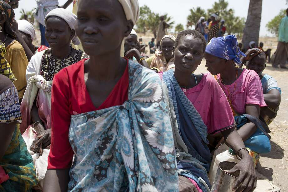 Women wait for food to be distributed in Leich state. The U.N. says the government blocks such aid. Photo: Charles Atiki Lomodong, Associated Press