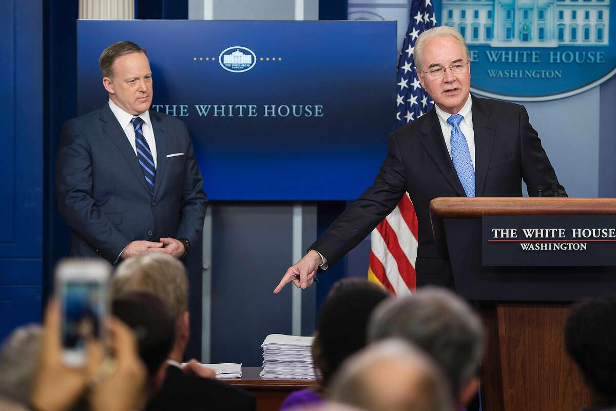 White House Press Secretary Sean Spicer (L) looks on as US Secretary of Health and Human Service Tom Price (R) points to a print-out of the Affordable Care Act (ACA) and a copy of the new plan introduced to repeal and replace the ACA during the daily briefing at the White House in Washington, DC on March 7, 2017. / AFP PHOTO / JIM WATSONJIM WATSON/AFP/Getty Images