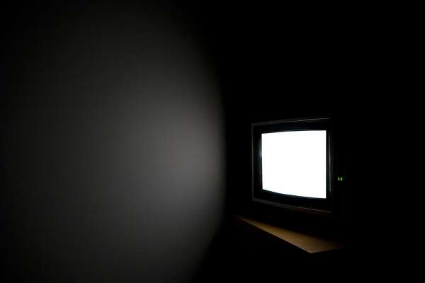 Television set glowing in a dark room.