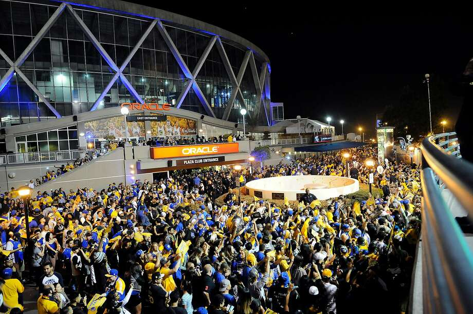 Fans who attended a Game 6 Warriors watch party dance outside Oracle Arena after the Golden State Warriors won the NBA championship at Oracle Arena in Oakland on June 16, 2015. Oakland officials get free tickets to every Warriors game. Photo: Michael Short, Special To The Chronicle
