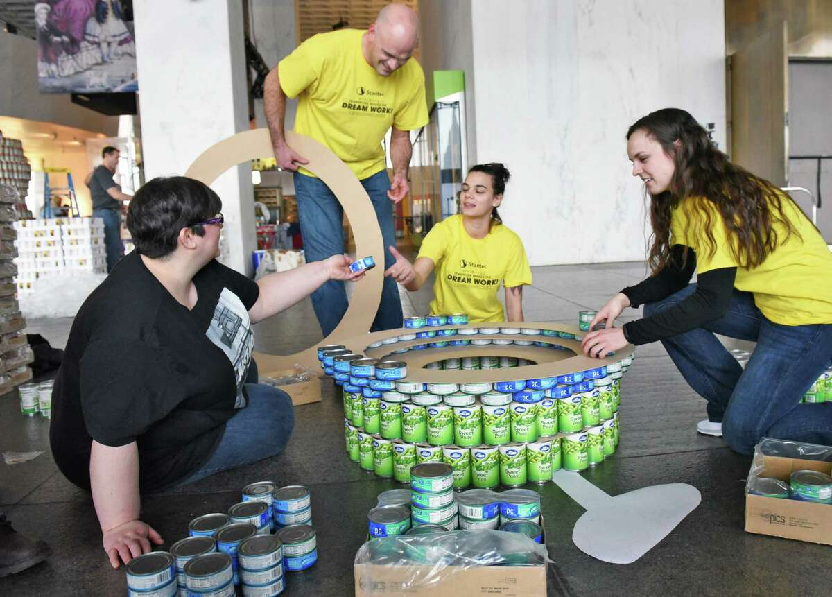 Team Stantec members, from left, Marla Hoyt, Chris Persbacker, Kate Miller and Bailiei Tetrault work on a giant soccer ball construction as teams from local architecture, engineering and construction firms, as well as design students, build massive structures made entirely out of canned goods at the New York State Museum to benefit The Food Pantries for the Capital District Tuesday March 7, 2017 in Albany, NY. (John Carl D'Annibale / Times Union)