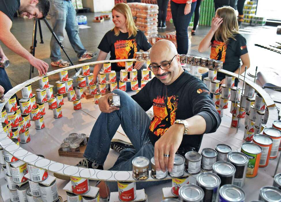 MJ Engineering's Nathaniel Gibson, center, works on their Slam Dunk Hunger structure as teams from local architecture, engineering and construction firms, as well as design students, build massive structures made entirely out of canned goods at the New York State Museum to benefit The Food Pantries for the Capital District Tuesday March 7, 2017 in Albany, NY. (John Carl D'Annibale / Times Union)
