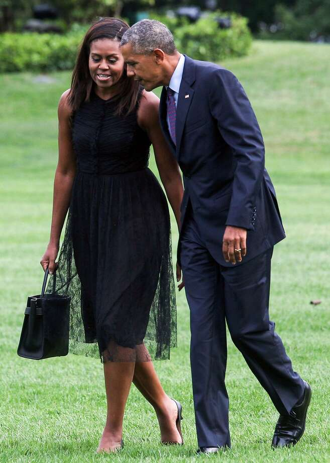(FILES) This file photo taken on September 21, 2016 shows  First Lady Michelle Obama and President Barack Obama arriving at The White House in Washington, DC.   New York based publisher Penguin Random House has won the industry's most coveted contract: a two-for-one deal to produce the memoirs of former president Barack Obama and first lady Michelle Obama. Bidding for the high-profile double book deal topped $60 million, a record sum for US presidential memoirs, according to the Financial Times. / AFP PHOTO / ZACH GIBSONZACH GIBSON/AFP/Getty Images Photo: ZACH GIBSON, AFP/Getty Images