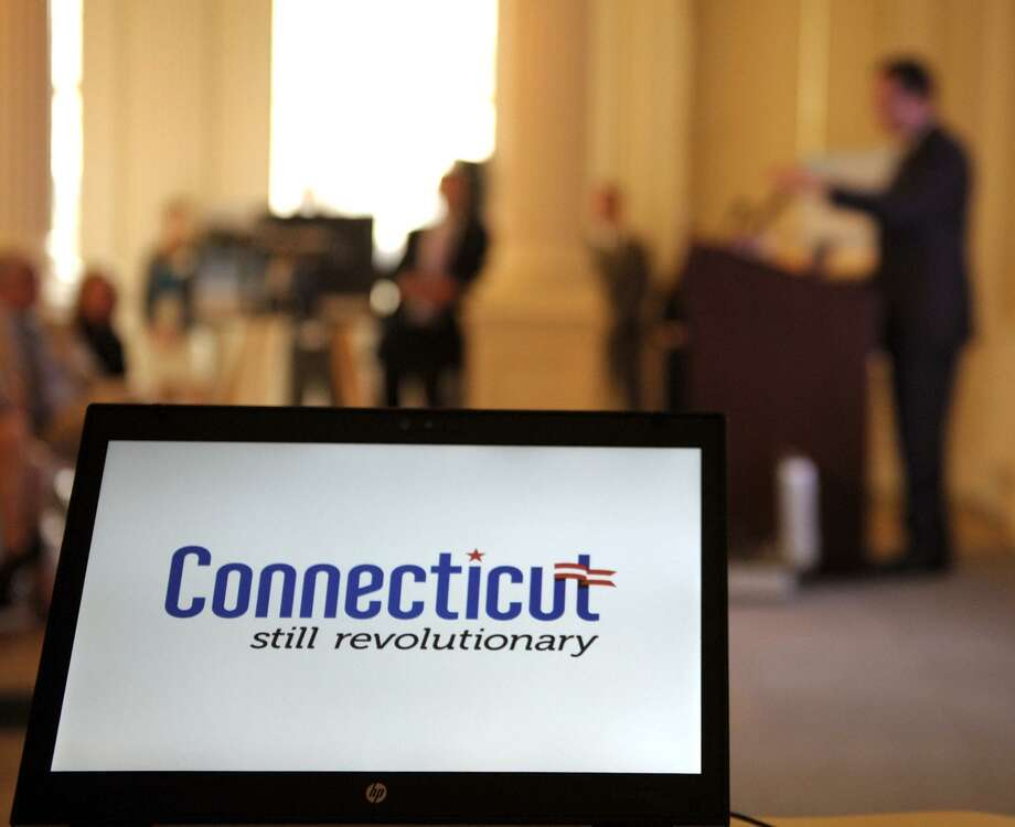 "A ""Still Revolutionary"" logo is displayed on a laptop computer projecting onto a screen on stage as Connecticut Gov. Dannel P. Malloy speaks during an unveiling of a tourism branding campaign in 2012. Photo: Sean D. Elliot / The Day Via AP / 2012 The Day Publishing Company"