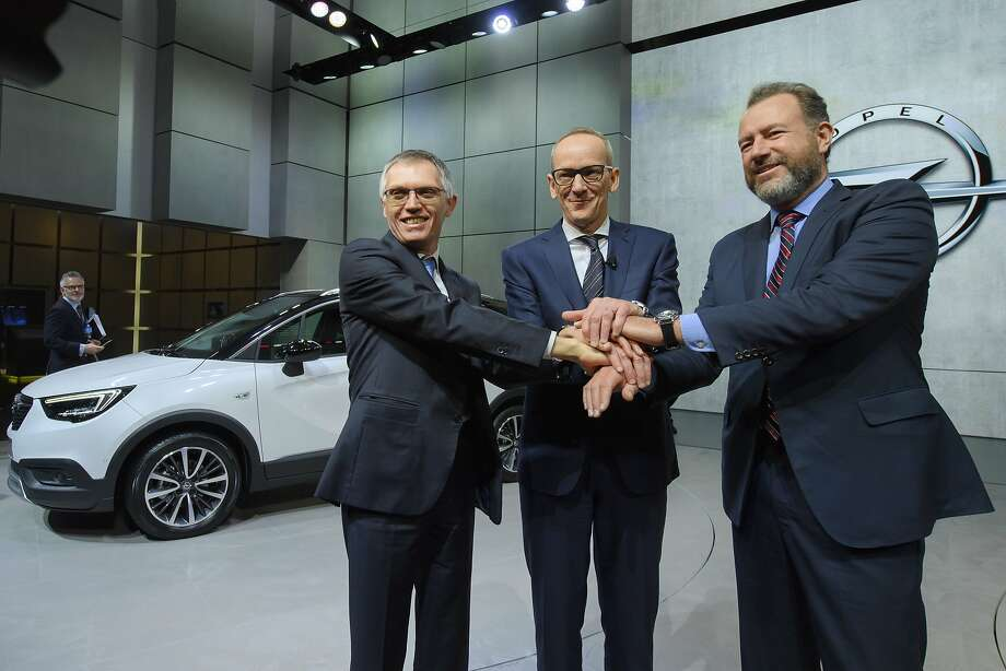 Carlos Tavares (left), CEO of PSA Peugeot Citroen; Karl-Thomas Neumann, CEO of Opel Group; and GM President Dan Ammann shake on the deal sending the Opel and Vauxhall brands from GM to PSA. Photo: Martial Trezzini, Associated Press