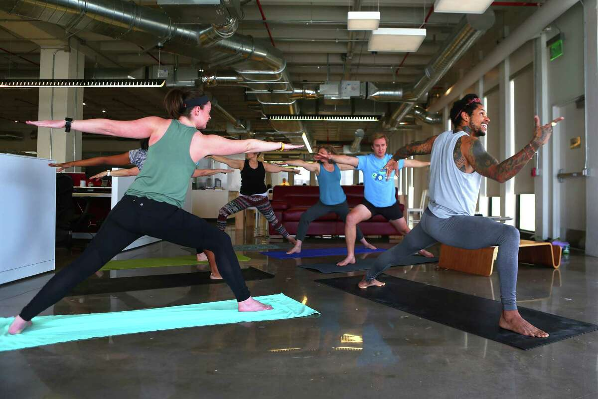 BIG Power Yoga instructor Juan Valentine leads Houston Chronicle staff members through a flow inside the Chronicle's newsroom, Wednesday, March 1, 2017, in Houston.