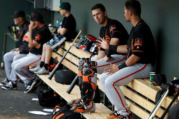 San Francisco Giants catcher Buster Posey, center, talks with teammate Joe Panik in the dugout during a Spring Training game against the Oakland Athletics at Hohokam Stadium in Mesa, AZ. on Friday, March 3, 2017.  With the hyper-partisan political climate, players are hesitant to talk politics or voice their views in order to keep team unity and chemistry in the clubhouse.