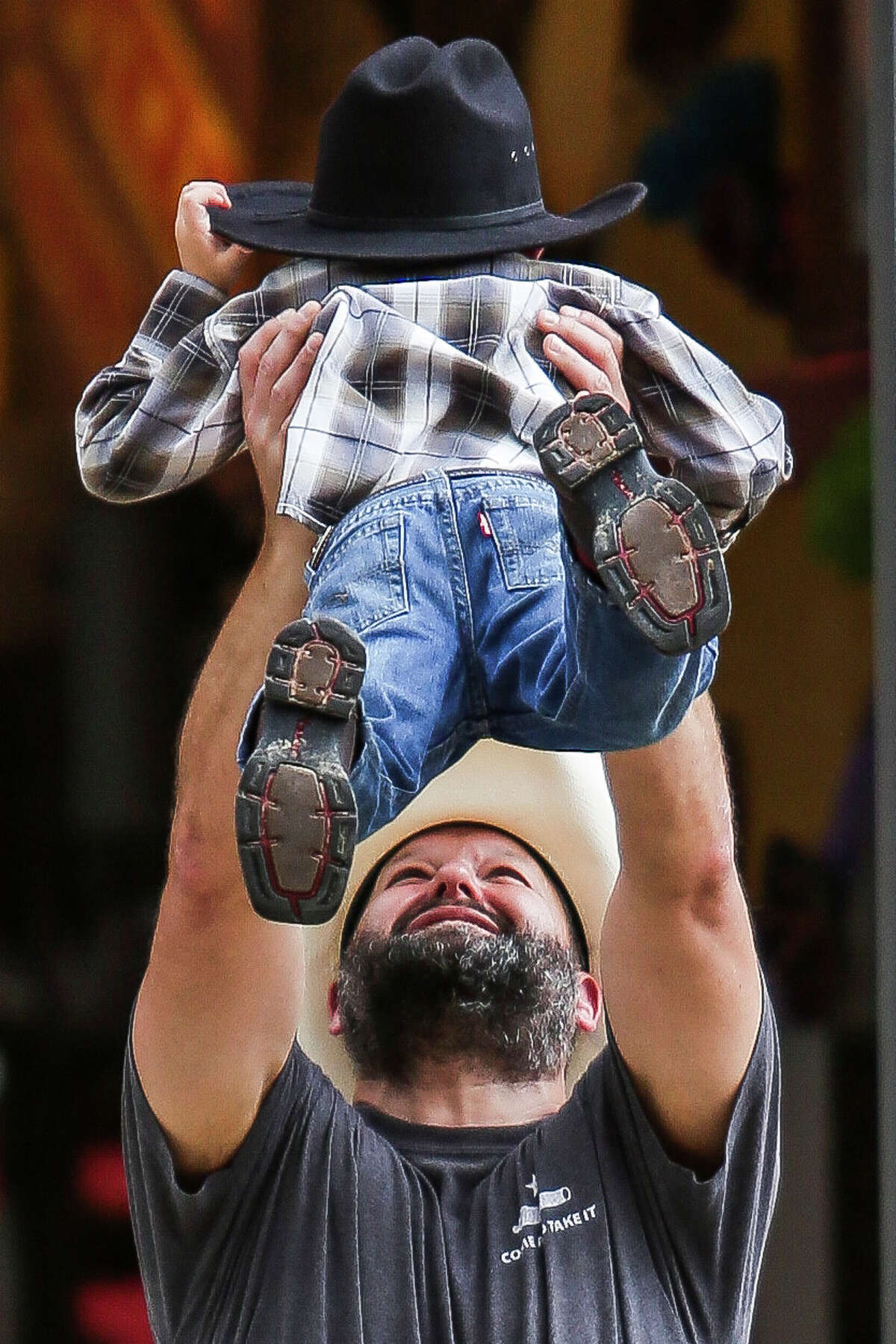 Travis Mann lifts his son, Jackson Mann, 5, in the air on the opening day of the Houston Livestock Show and Rodeo Tuesday, March 7, 2017 in Houston.