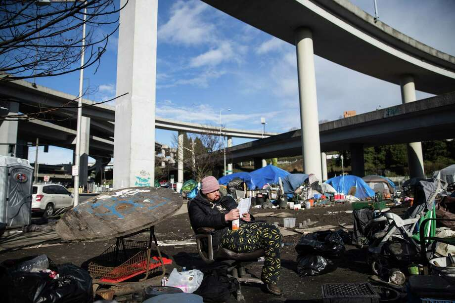 "A man known as ""Jim"" reads a library pamphlet in the so-called ""Field of dreams,"" a homeless encampment under the I-90 overpass in Sodo before the upcoming clearing, on Monday, March 6, 2017. The city of Seattle cleared the camp due to health hazards on Tuesday morning. Photo: GRANT HINDSLEY, SEATTLEPI.COM / SEATTLEPI.COM"