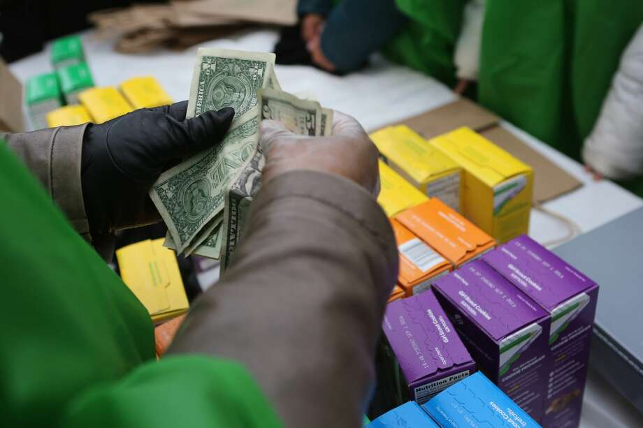NEW YORK, NY - FEBRUARY 08:  MOney is collected as Girl Scouts sell cookies while a winter storm moves in on February 8, 2013 in New York City. The scouts did brisk business, setting up shop in locations around Midtown Manhattan on National Girl Scout Cookie Day.  (Photo by John Moore/Getty Images) Photo: John Moore/Getty Images