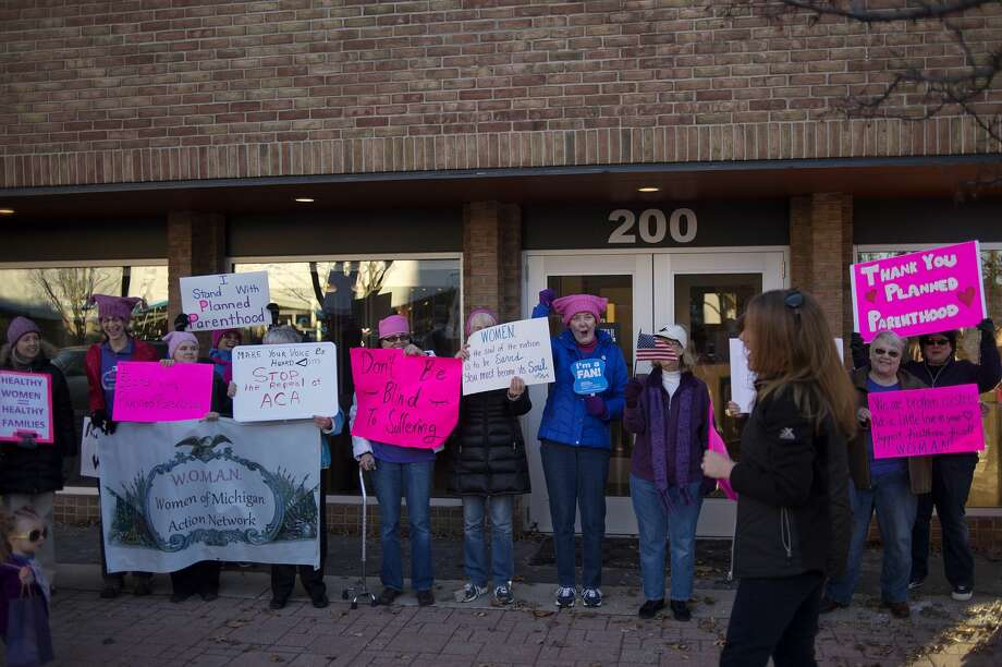 BRITTNEY LOHMILLER | blohmiller@mdn.net Sarah Schultz, with The Women of Michigan Action Network, leads a group of 36 people in a chant outside of U.S. Congressman John Moolenaar's Midland office Tuesday afternoon. The group gathered to protest after the House of Representatives voted to repeal the Affordable Care Act, including defunding Planned Parenthood. Photo: Brittney Lohmiller/Midland Daily News/Brittney Lohmiller