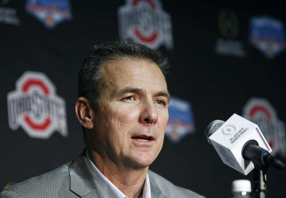 FILE - In this Monday Dec. 26, 2016, file photo, Ohio State head coach Urban Meyer speaks to the media after arriving with his team at Phoenix Sky Harbor Airport in Phoenix. Once seen as a luxury of the corporate world, private planes are becoming increasingly common at U.S. colleges and universities as schools try to attract athletes, raise money and reward coaches with jet-set vacations. At Ohio State University, which leases one plane and partly owns another, Meyer and members of his family took more than 10 personal trips last school year, including a vacation in Florida, a weekend getaway to Cape Cod and a spring break in South Carolina. (AP Photo/Ralph Freso, File) Photo: Ralph Freso, Associated Press