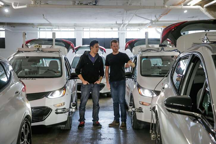 Co-founders Daniel Kan and Kyle Vogt (right) chat about a car as they stand for a portrait at Cruise Automation in San Francisco, California, on Tuesday, March 7, 2017.