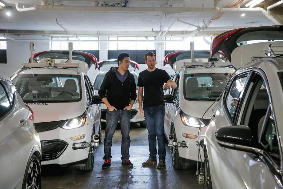Cruise Automation co-founders Daniel Kan and Kyle Vogt (right) chat about a self-driving car in the GM-owned unit's San Francisco garage. Photo: Gabrielle Lurie, The Chronicle