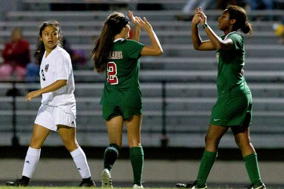 The Woodlands midfielder Kate McCullough (2) celebrates with after midfielder Jazzy Richards (16) her fourth goal of the game during a District 12-6A high school soccer match at Buddy Moorhead Stadium Tueday in Conroe.  The Woodlands defeated Conroe 9-1.