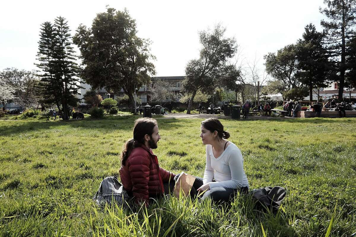 Oakland residents Eric Hertz and Maggie Medlin, relax in the grass at People's Park in Berkeley, CA, on Tuesday March 7, 2017.
