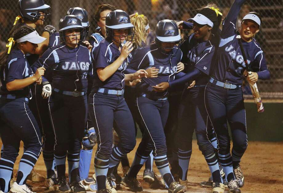 Johnson's Mia Moreno (third from right) is congratulated by her teammates after hitting a grand slam against MacArthur in in the second inning at NEISD Complex's West Field on March 7, 2017. Photo: Kin Man Hui /San Antonio Express-News / ©2017 San Antonio Express-News
