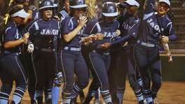 Johnson's Mia Moreno (third from right) is congratulated by her teammates after hitting a grand slam against MacArthur in in the second inning at NEISD Complex's West Field on March 7, 2017.