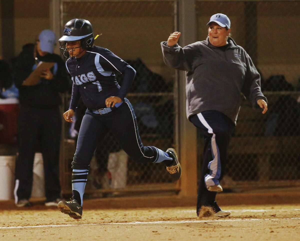 Johnson's Mia Moreno (07) gets congratulated by Johnson coach Jennifer Fox (right) as she rounds third base after hitting a two-run homer in the first inning against MacArthur in girls softball at NEISD Complex's West Field on Tuesday, Mar. 7, 2017. Johnson is No. 1 and MacArthur is No. 2 in Express-News Area rankings. (Kin Man Hui/San Antonio Express-News)