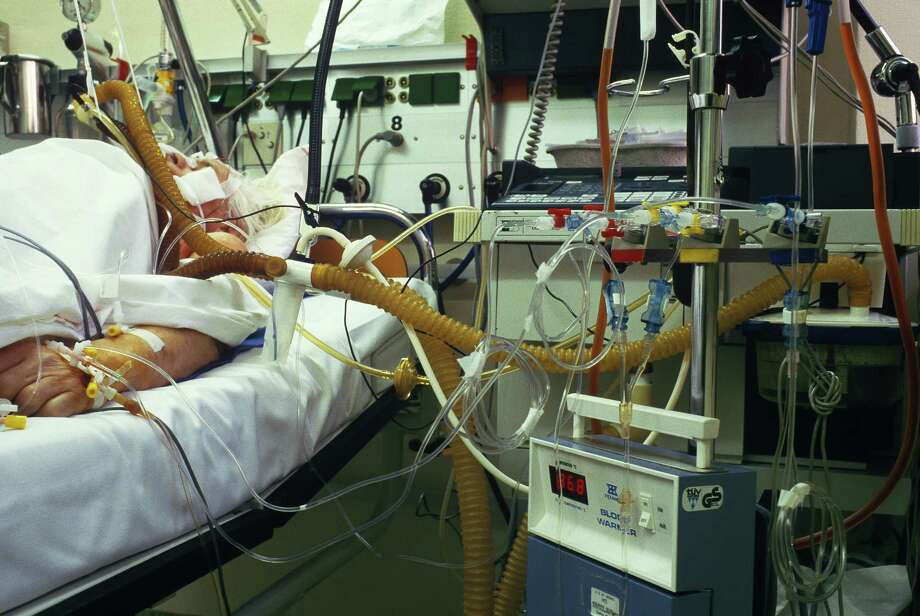 """The """"End-of-Life Conveyor Belt"""": Dying patients are kept alive by  machines,alone in a cold and sterile environment, their arms strapped  down to the bed so that their catheters aren't dislodged. Photo: Getty Images, Jan Halaska / This content is subject to copyright."""
