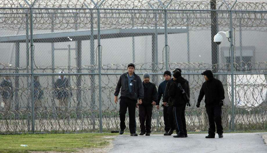 -Correctional guards at the Willacy County Correctional Center in Raymondville, Texas walk the perimeter Saturday Feb.21, 2015 near where the uprising took place early Friday the  facility Saturday, Feb.21, 2015. In the background inmates keep a watchful eye. Photo by Delcia Lopez Photo: Delcia Lopez, MBR / AP / Delcia Lopez photography