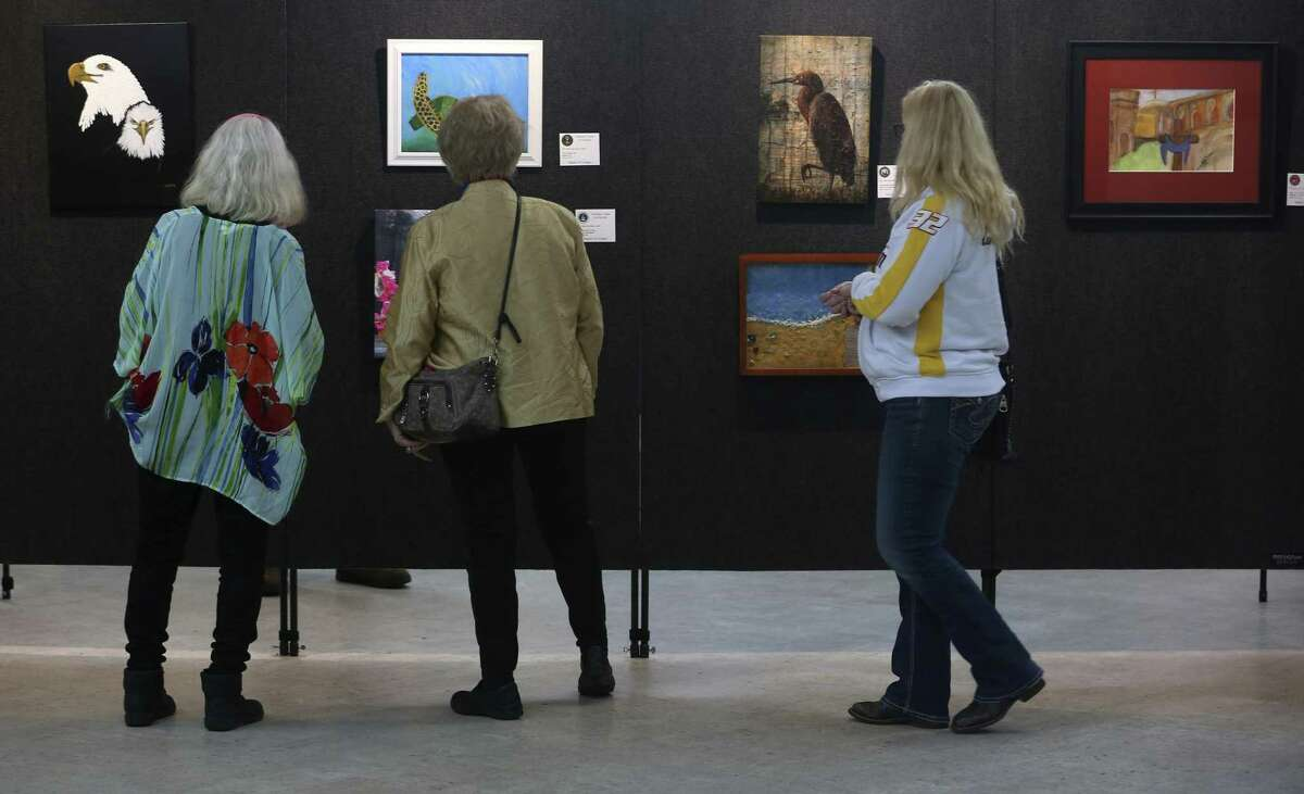 People view some of the more than 75 artworks by about 35 military veteran artists on display Tuesday, March 7, 2017 at the H. U. Wood Post 245 American Legion Hall in Sequin on the first day of an exhibit sponsored by the Sequin Art League.