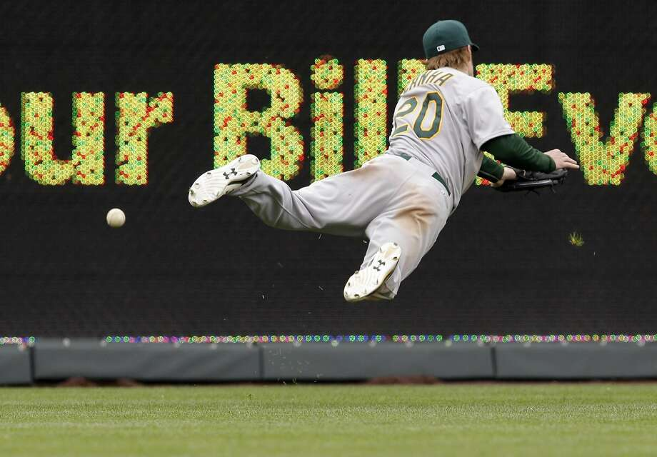 Oakland Athletics left fielder Mark Canha (20) dives for a ball hit by Kansas City Royals' Lorenzo Cain during the eighth inning of a baseball game at Kauffman Stadium in Kansas City, Mo., Sunday, April 19, 2015. The Royals defeated the Athletics 4-2. (AP Photo/Orlin Wagner) Photo: Orlin Wagner, Associated Press