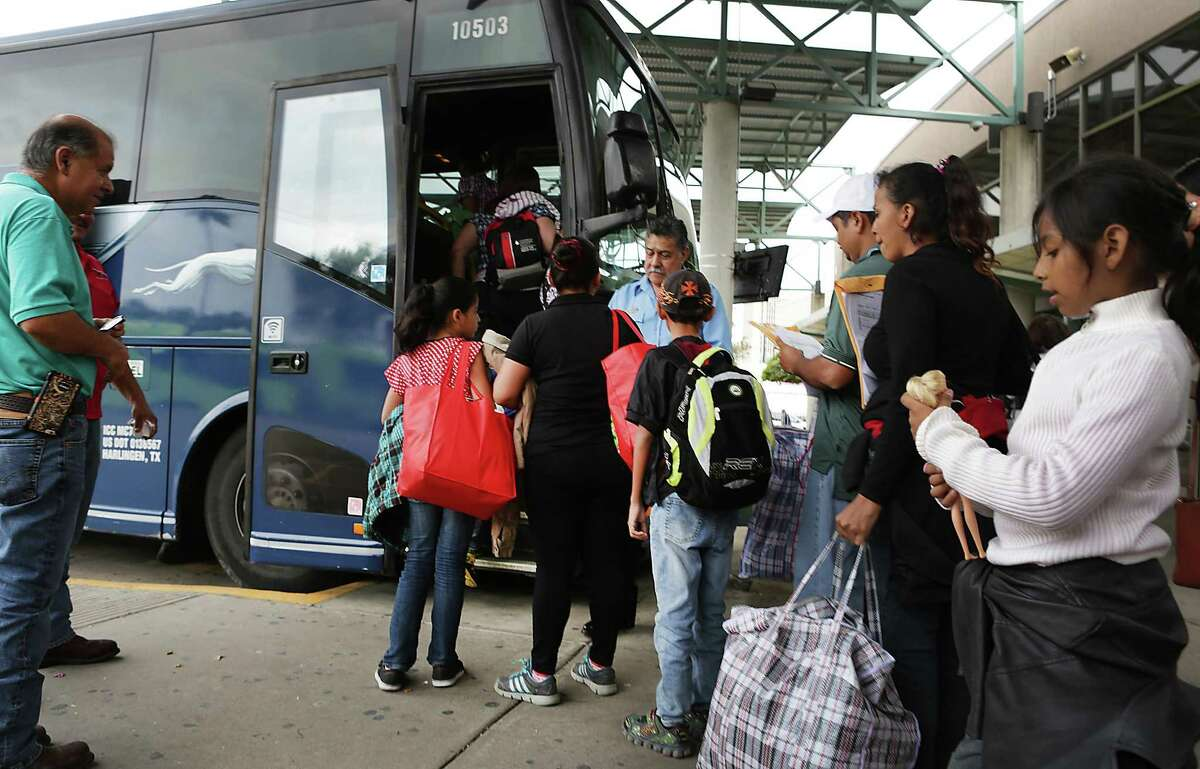 A group of immigrants from Central America is assisted by Sacred Heart Project Director Eli Fernandez, left, as they board a bus in McAllen, TX, on Tuesday, Dec. 27, 2016, traveling to join family members already in the U.S.