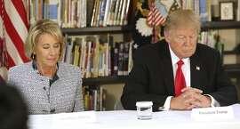President Donald Trump, right, and U.S. Secretary of Education Betsy DeVos close their eyes in prayer during their visit to St. Andrew Catholic School n Orlando, Fla., Friday, March 3, 2017. (Joe Burbank/Orlando Sentinel via AP)