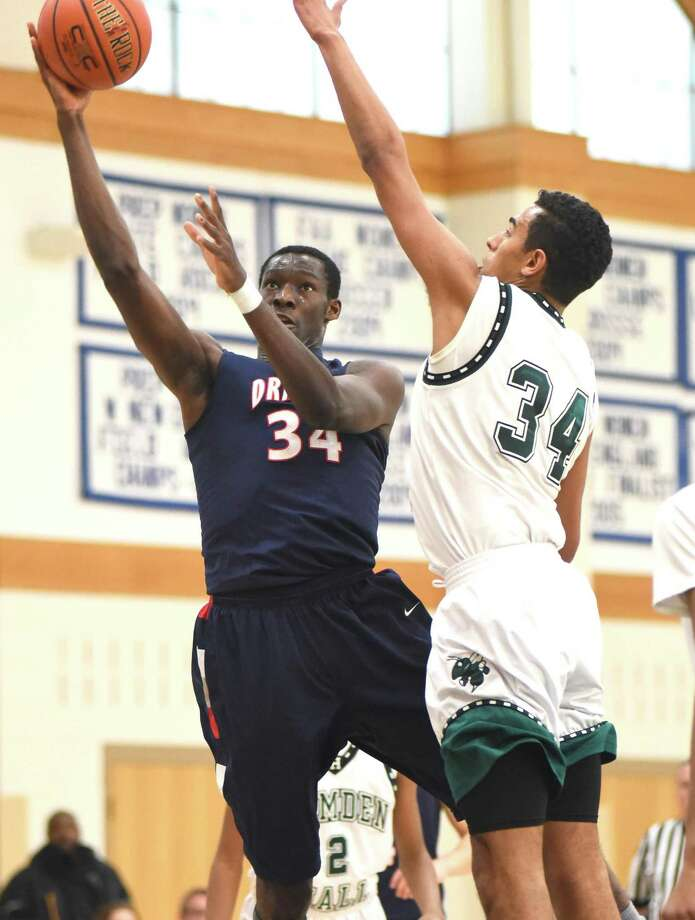 Greens Farms Academy's Sunday Okeke, left, puts up a shot against Hamden Hall defender Dan Draffan during the first half of Saturday's NEPSAC Class C semifinal tournament game at Coyle Gym in Westport. Behind Okeke's triple double of 19 points, 20 rebounds and 10 blocked shots, host GFA defeated Hamden Hall 68-57. Photo: John Nash / Hearst Connecticut Media / Norwalk Hour
