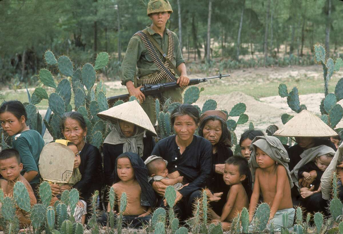 Jan. 1, 1965 : American Marine guarding mostly old people and children who are resting on their way to a refugee collection point during the Vietnam War.