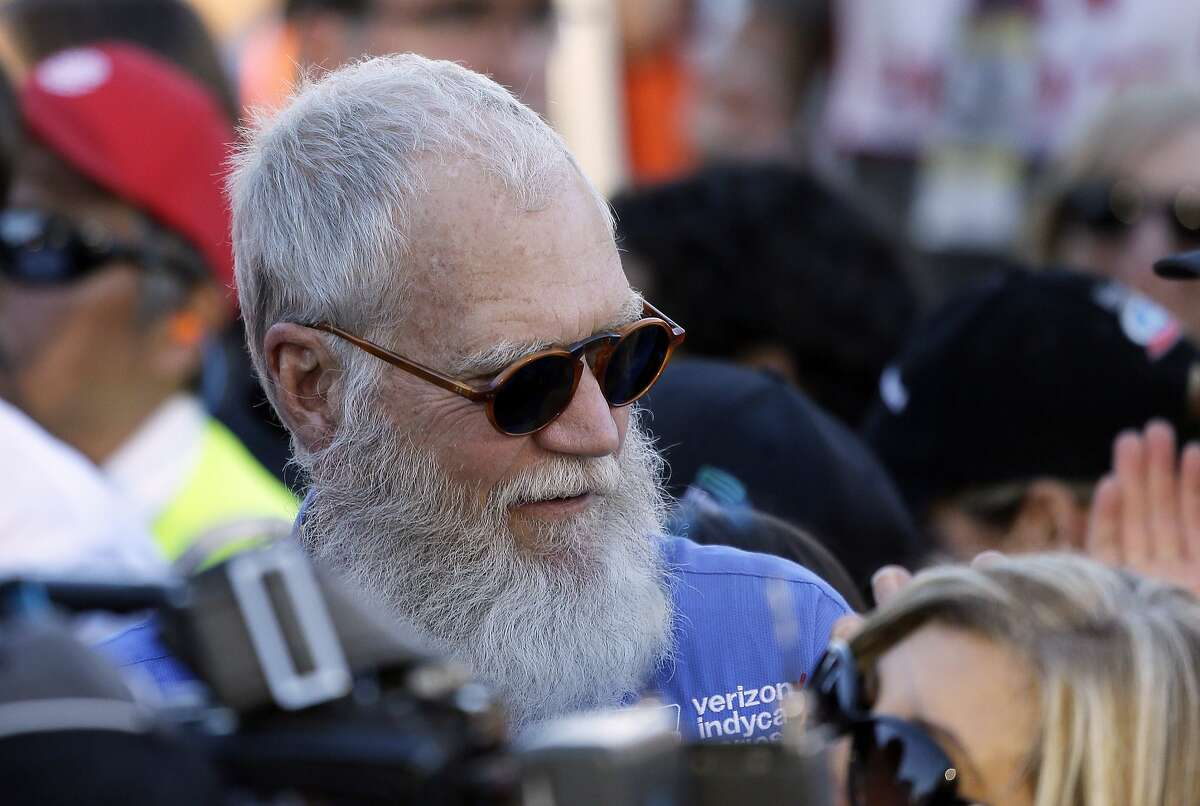 FILE - In this Sept. 18, 2016, file photo, David Letterman stands near victory lane and watches celebrations after the IndyCar auto race in Sonoma, Calif. Letterman tells Vulture in an interview published online on March 5, 2017, that says he would have handled President Donald Trump a bit differently than �Tonight Show� host Jimmy Fallon. (AP Photo/Eric Risberg, File)
