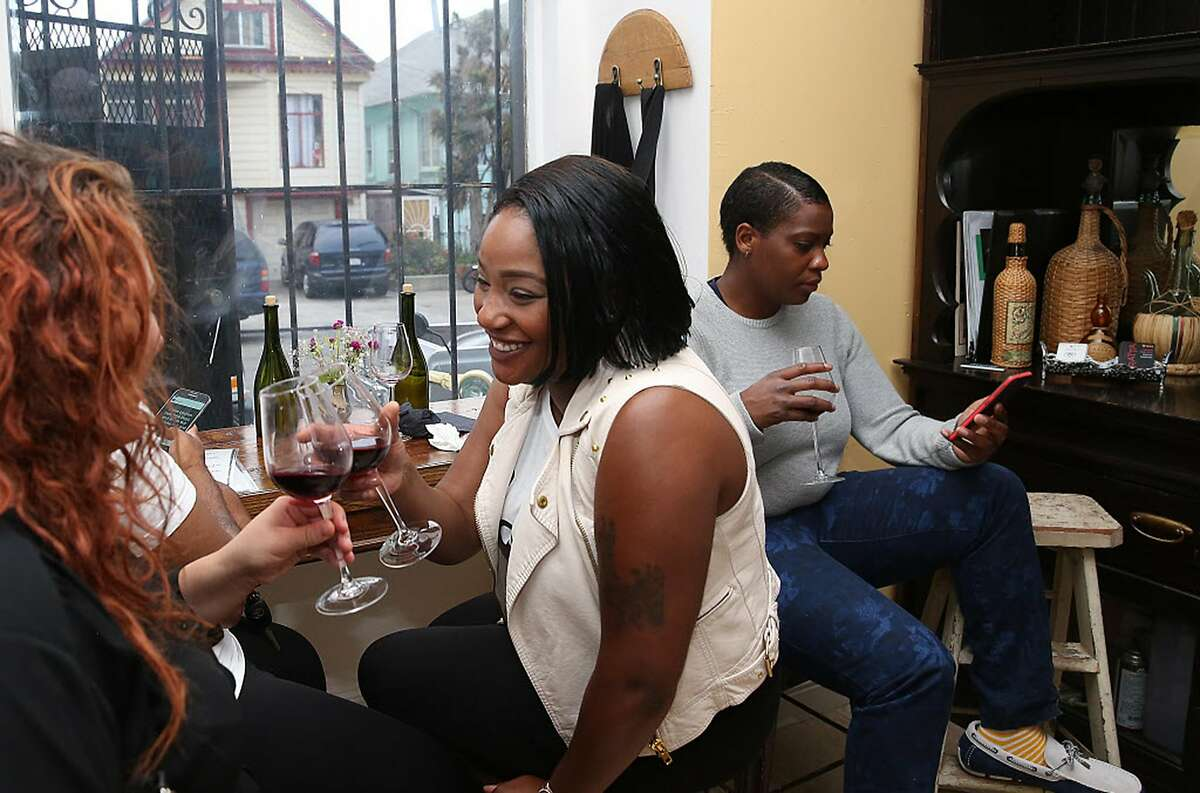 Kristin King (left), Tiffany Green (middle), and Tazia Harris (right) have Gratta zinfandel at Butchertown Gourmet during Pizza and Wine night in San Francisco, Calif., on Friday, August 21, 2015.