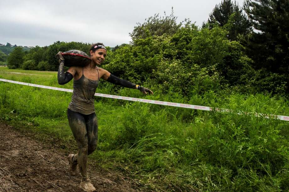 A female runner carries a sandbag during the Reebok Spartan Race, a race in mud with multiple obstacles, in Jablines, France on June 04, 2016. Photo: Anadolu Agency/Getty Images
