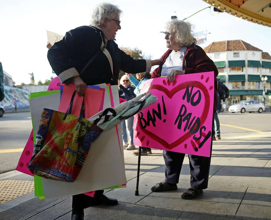 Indivisible organizer Alice Phillips (left) greets Margaret Hasselman at the weekly rally against President Trump in Oakland. Photo: Scott Strazzante, The Chronicle