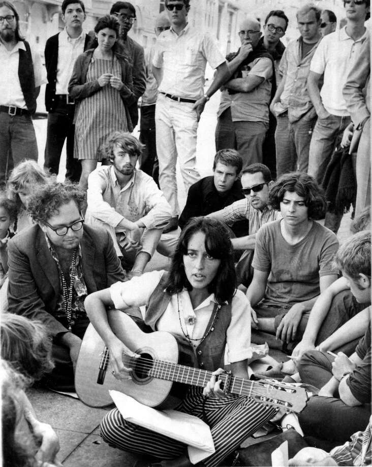 FILE - In this Sept. 22, 1967, file photo, folk singer Joan Baez sits at the corner of Haight and Ashbury in San Francisco, serenading hippies and tourists. City officials have rejected a permit for a planned free concert intended to mark the 50th anniversary of the famed Summer of Love in Golden Gate Park that had been planned for June 2017. (AP Photo/File) Photo: Associated Press