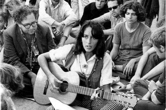 FILE - In this Sept. 22, 1967, file photo, folk singer Joan Baez sits at the corner of Haight and Ashbury in San Francisco, serenading hippies and tourists. City officials have rejected a permit for a planned free concert intended to mark the 50th anniversary of the famed Summer of Love in Golden Gate Park that had been planned for June 2017. (AP Photo/File)