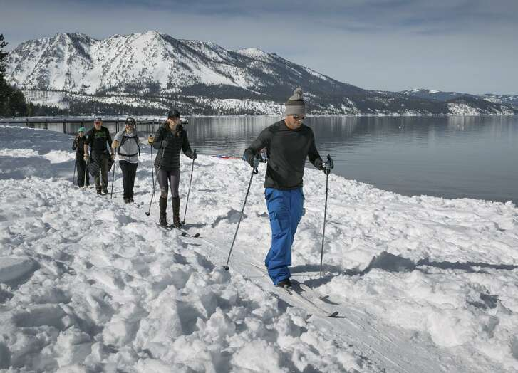 Cross-country skiers make their way along a lake trail near South Lake Tahoe. Heavy snow means snow-sport recreation will be continuing for weeks and, in places, months.