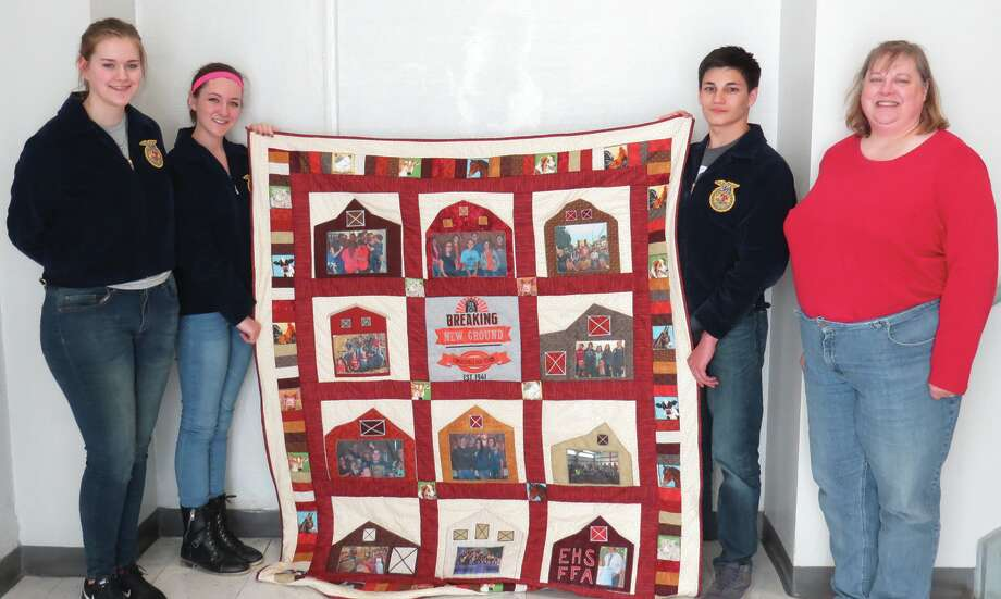 FFA members Katie Hajny, Sandy Hartnagel and Jack Eaker stand with Bonnie Hajny and the quilt she made for the FFA Alumni Auction. The quilt is one of several items up for auction at the fundraiser.