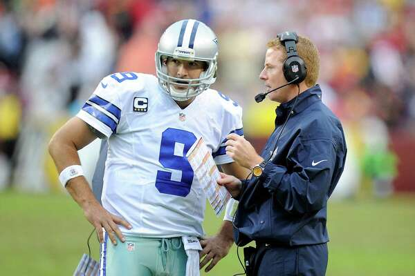 Head coach Jason Garrett of the Dallas Cowboys talks with Tony Romo during a timeout in the fourth quarter against the Washington Redskins at FedExField on Dec. 22, 2013 in Landover, Md.