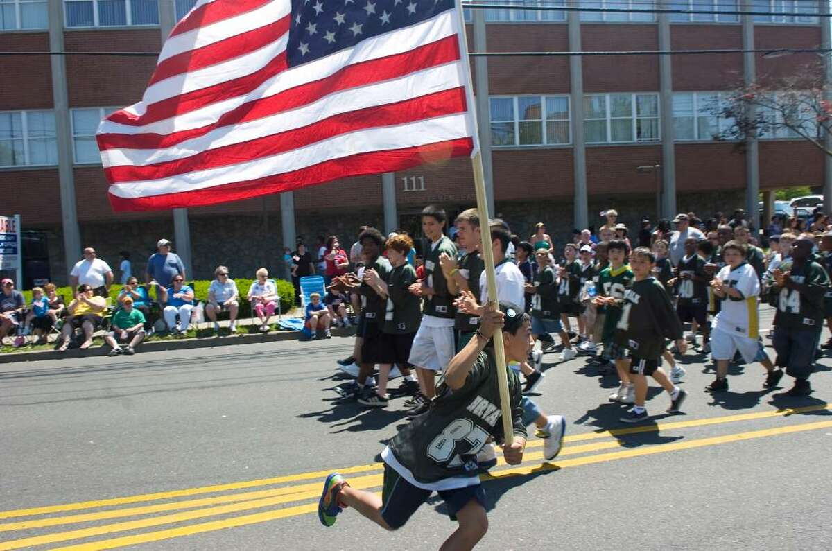 Sebastian Corren, 11, parades with the Norwalk Youth Football League during Norwalk's Memorial Day Parade from Veterans Memorial Park on Seaview Ave, along Van Zant Street and up East Avenue to the Town Green, Monday May 31, 2010.