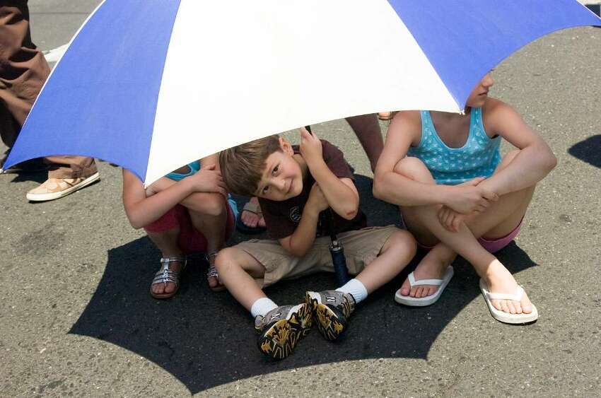 Jagger Opalinski, 4, keeps the sun at bay while watching Norwalk's Memorial Day Parade from Veterans Memorial Park on Seaview Ave, along Van Zant Street and up East Avenue to the Town Green, Monday May 31, 2010.
