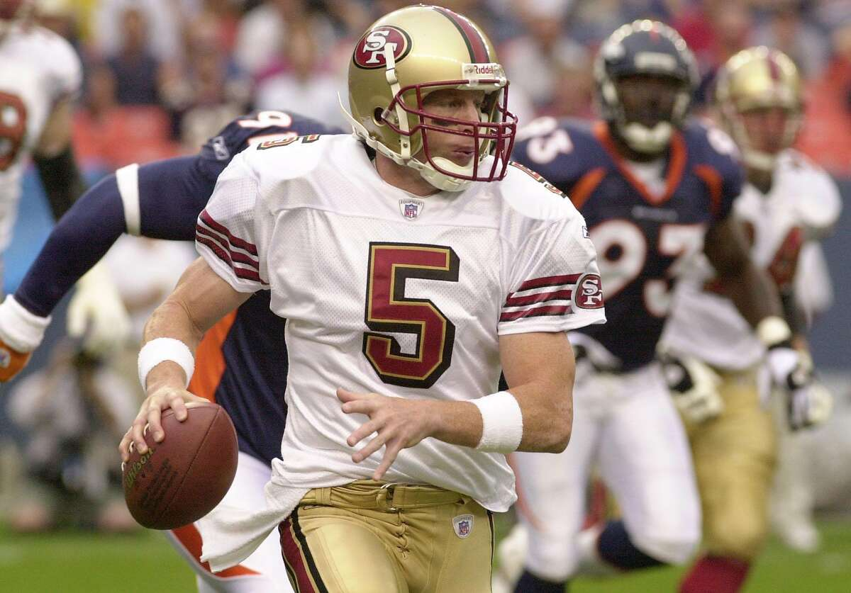 San Francisco quarterback Jeff Garcia scrambles to the sidelines as he his chased by Denver defenders Chike Okeafor (91) and John Schlecht during the first quarter of their exhibition game in Denver on Monday night, August 19, 2002. (AP Photo/Ed Andrieski)
