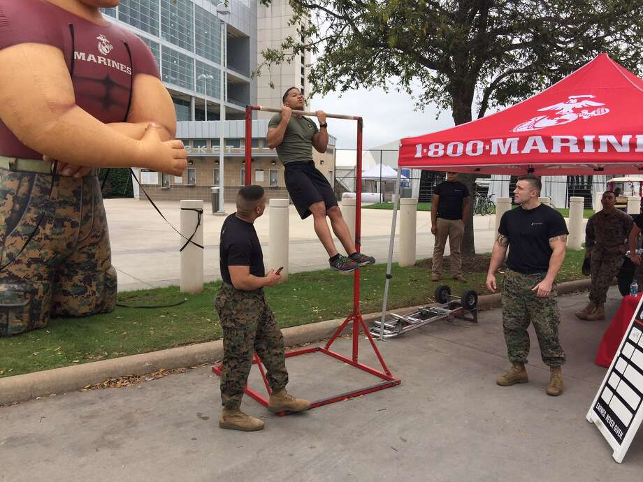 At the Marines' rodeo display, Army recruit Dejon Jackson does pull-ups. Photo: Mike Glenn