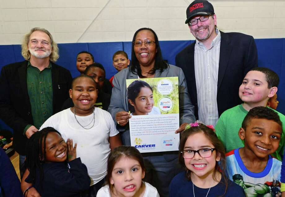 """Musician Tom """"The Suit"""" Forst, George Washington Carver Community Center Executive Director Novelette Peterkin, and Norwalks Factory Underground Marc Alan pose with Carver program children to publicize the live music telethon they are producing for the Fairfied County Giving Day next week during a meeting Friday, March 3, 2017, at the Carver Center in Norwalk, Conn. The live music telethon will help them raise money in an effort to get top honors during Fairfied County Giving Day on March 9th which will award $20,000 to the non-profit that raises the most money. The telethon is going to feature live musicians and performers from all over CT including FNX, Edisun, Che-Val, Tom The Suit Forst, Brian Larney of Lines West, Berdine Joseph (Norwalk singer - finalist on Season 9 of The Voice) and will benefit Carver summer programs for children of low-income families in Norwalk. Photo: Erik Trautmann / Hearst Connecticut Media / Norwalk Hour"""