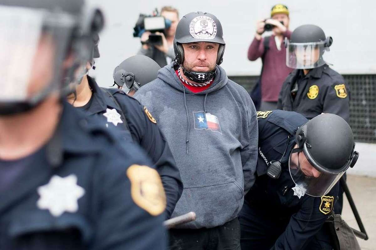 Police officers detain a pro-President Donald Trump demonstrator, Kyle Chapman in Berkeley, Calif., on Saturday, March 4, 2017.